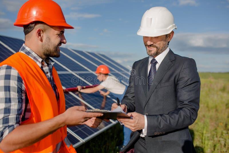 Cliënt die overeenkomst ondertekenen bij zonne-energiepost stock afbeelding