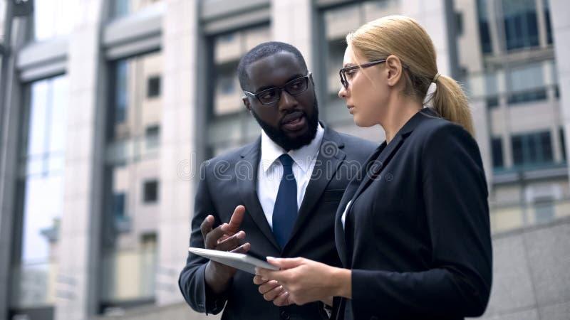 Cliënt en stafmedewerker die details van project op tablet, businessplan bespreken royalty-vrije stock afbeeldingen