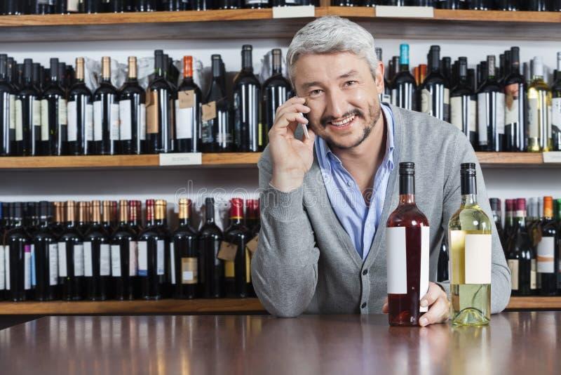 Client à l'aide du téléphone portable dans la boutique de vin photos libres de droits