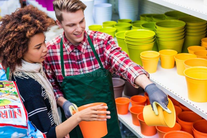 Client achetant les pots en plastique au conseil d'un travailleur utile photo libre de droits