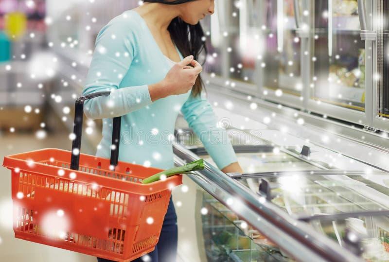 Client avec le panier de nourriture au congélateur d'épicerie photos stock