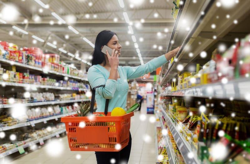 Client avec le panier de nourriture et smartphone au magasin photo stock