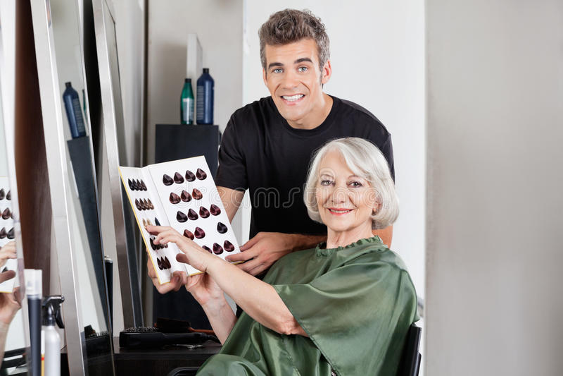 Client avec le styliste en coiffure tenant le catalogue de couleur photographie stock