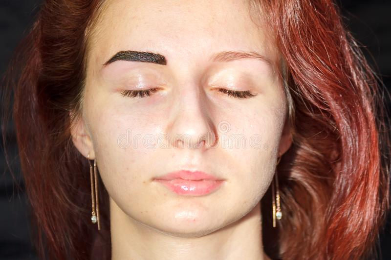 A client of a beauty parlor with one henna dyed with an eyebrow to compare the result. Horizontal photo stock photography