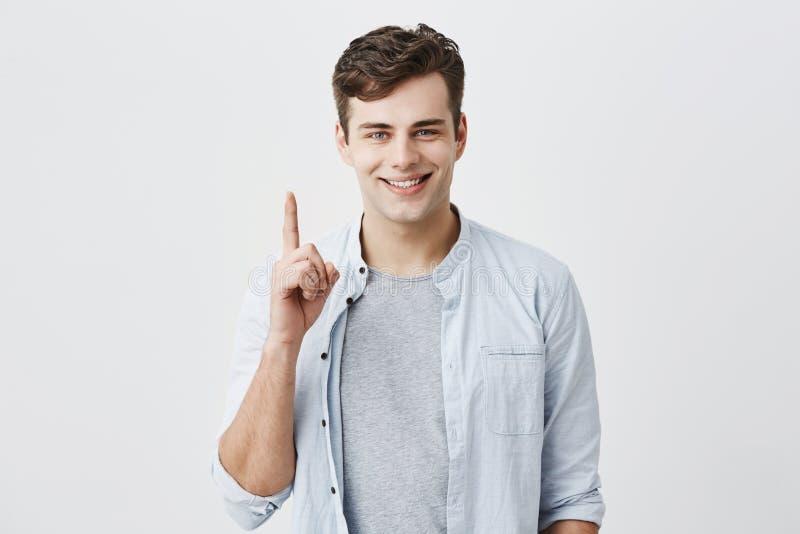 Client caucasien satisfaisant et heureux se dirigeant avec l'index à l'espace vide au-dessus pour votre publicité image libre de droits