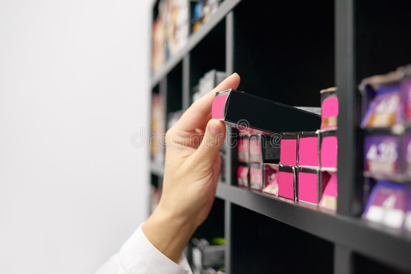 Client choosing hair care products in beaty salon. Little black boxes, packages with bright saturated pink etiquettes laying on wooden shelves on white stock images