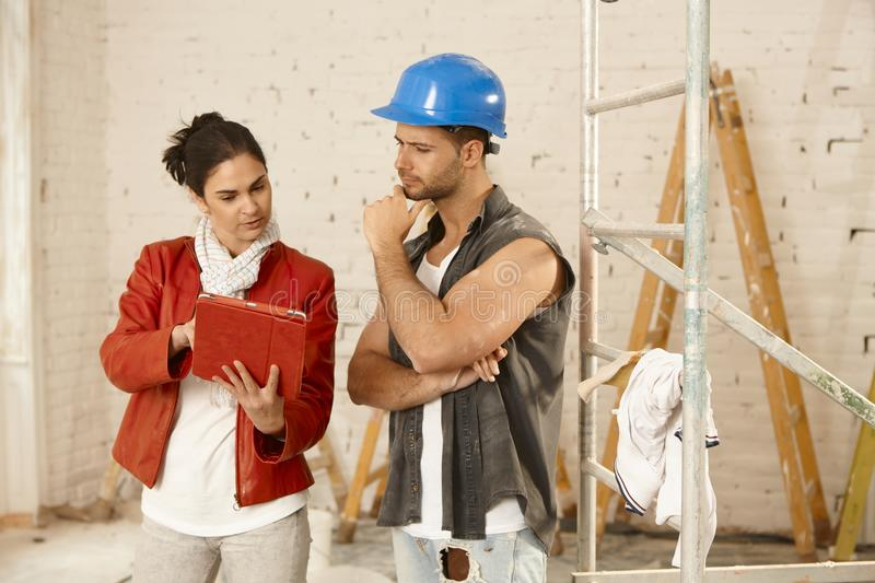 Client and contractor. Talking at renovation site, using tablet computer royalty free stock photos