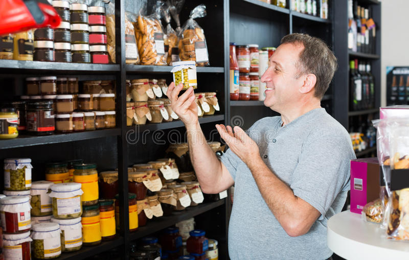 Client d'homme choisissant des produits dans la section d'épicerie fine photographie stock libre de droits