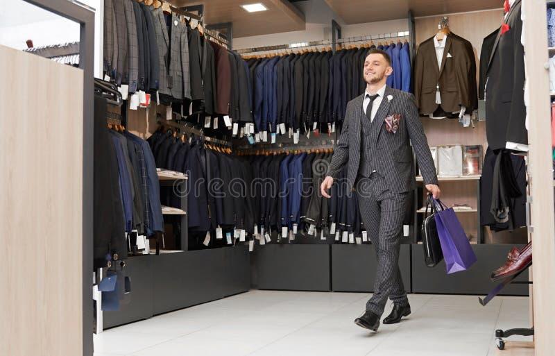 Client dans le costume dans la boutique avec des sacs à provisions images stock