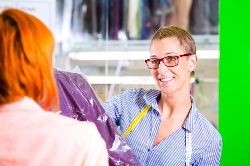 Client dans le nettoyage à sec de boutique ou de textile de blanchisserie photographie stock libre de droits