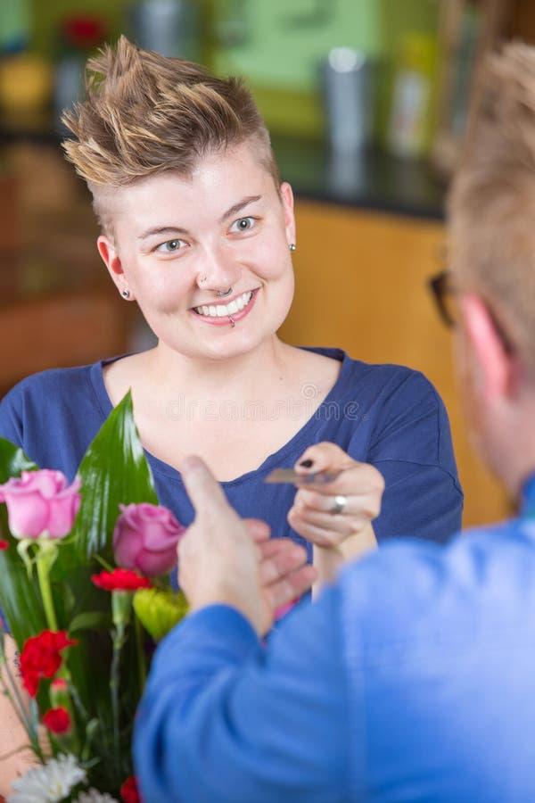 Client de sourire de fleuriste payant avec le crédit photos libres de droits