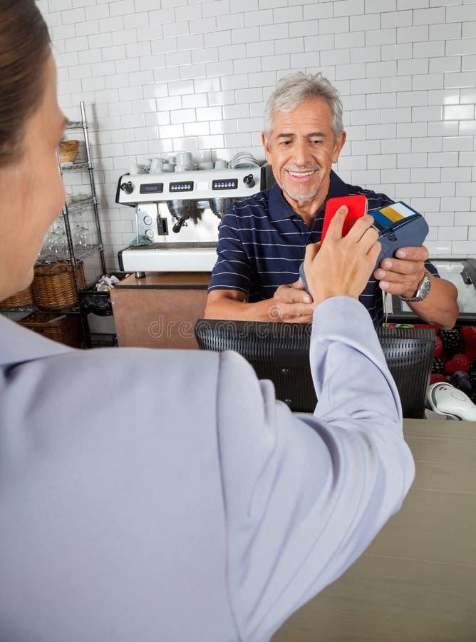 Client effectuant le paiement par le téléphone portable dedans photo libre de droits