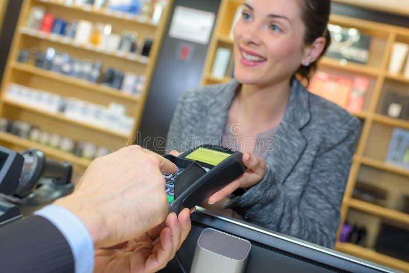 Client effectuant le paiement par le smartwatch dans la boutique de parfum photos libres de droits