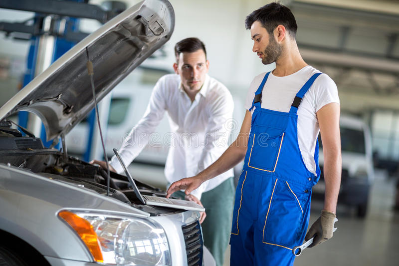 Client and employee looking diagnostic on engine stock images