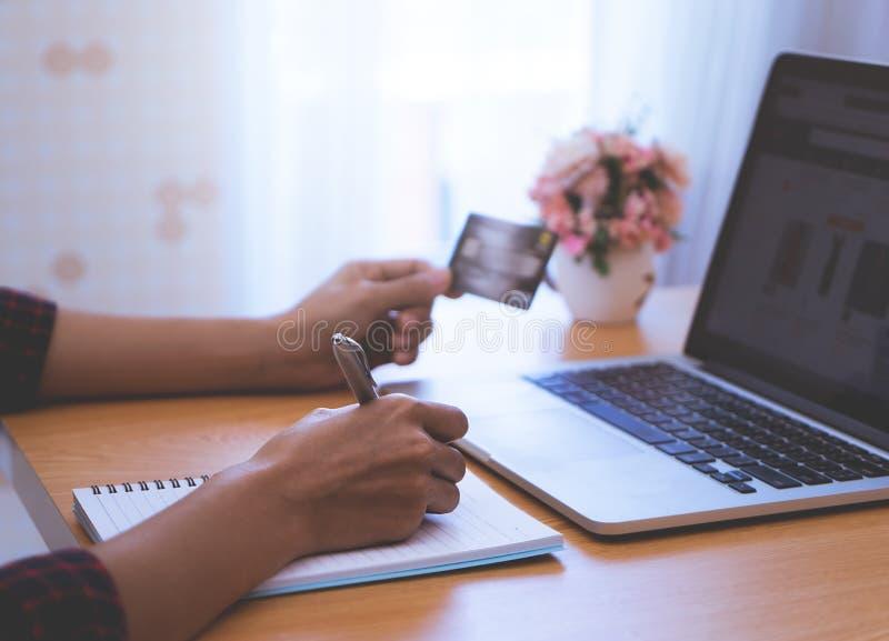Client en ligne avec la liste d'achats d'écriture de carte de crédit sur un livre photographie stock libre de droits