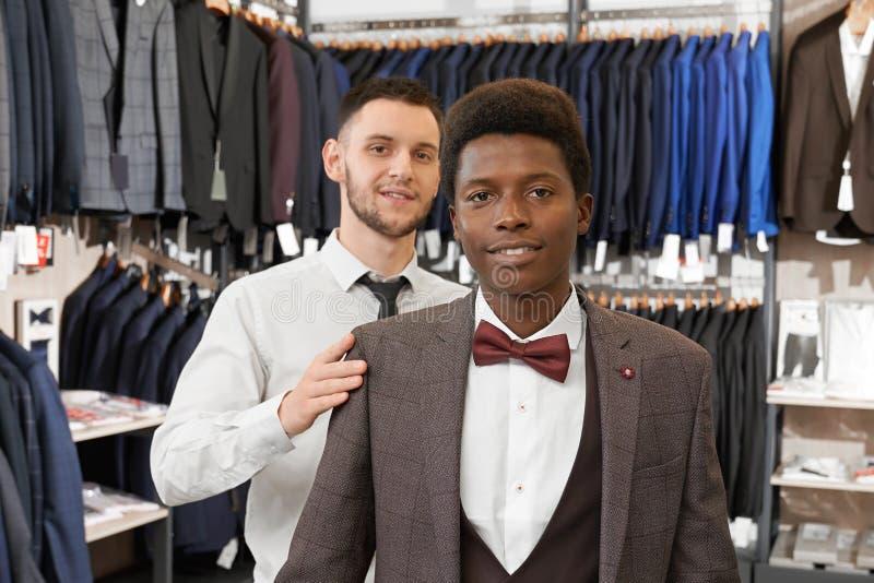 Client et assistant posant dans l'habillement élégant dans la boutique images stock
