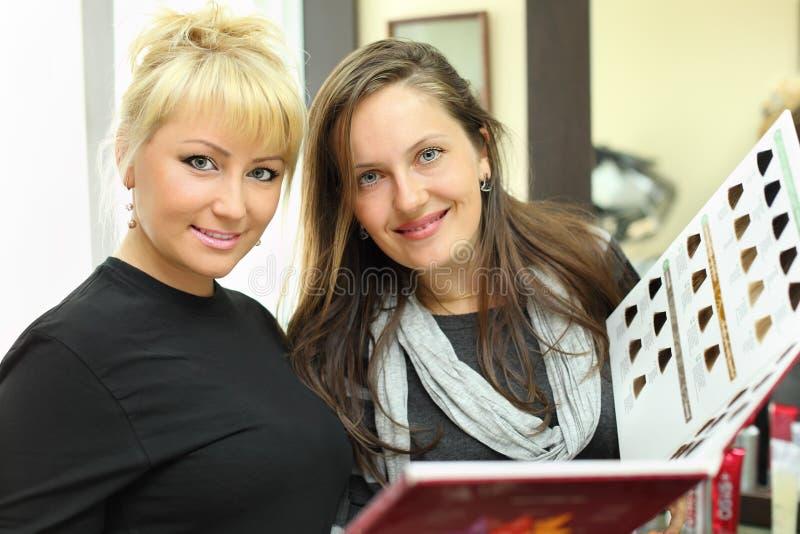Client et coiffeur avec le catalogue de couleurs de cheveu photos libres de droits