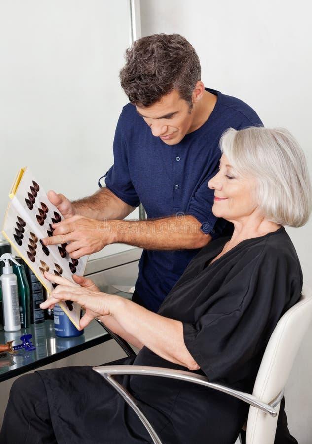 Client et styliste en coiffure sélectionnant la couleur de cheveux image stock