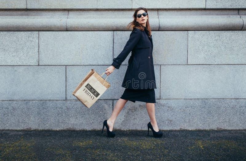 Client féminin élégant marchant avec le panier photographie stock libre de droits