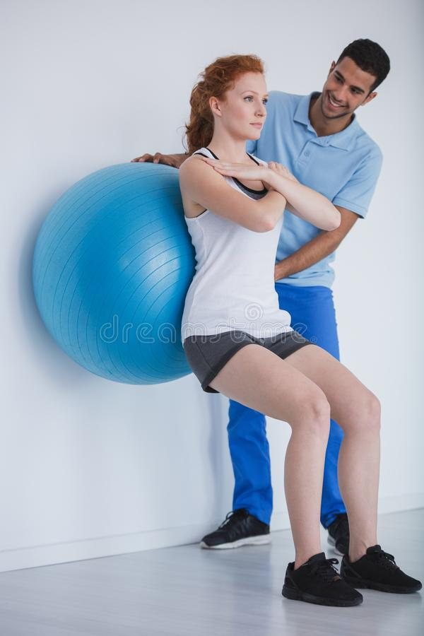 Client féminin établissant avec une boule pendant une formation avec un entraîneur personnel images libres de droits