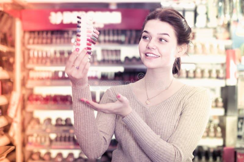 Client féminin attentif décidant des articles de maquillage en cosmétiques photo stock