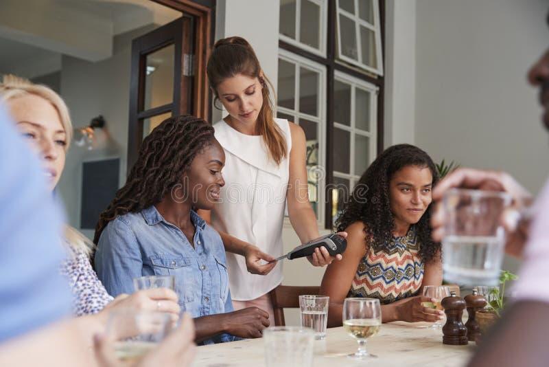 Client féminin dans le restaurant payant le terminal de Bill Using Contactless Credit Card photographie stock