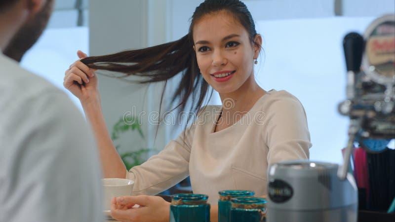 Client féminin de sourire flirtant avec le barman au compteur de barre en café photo libre de droits