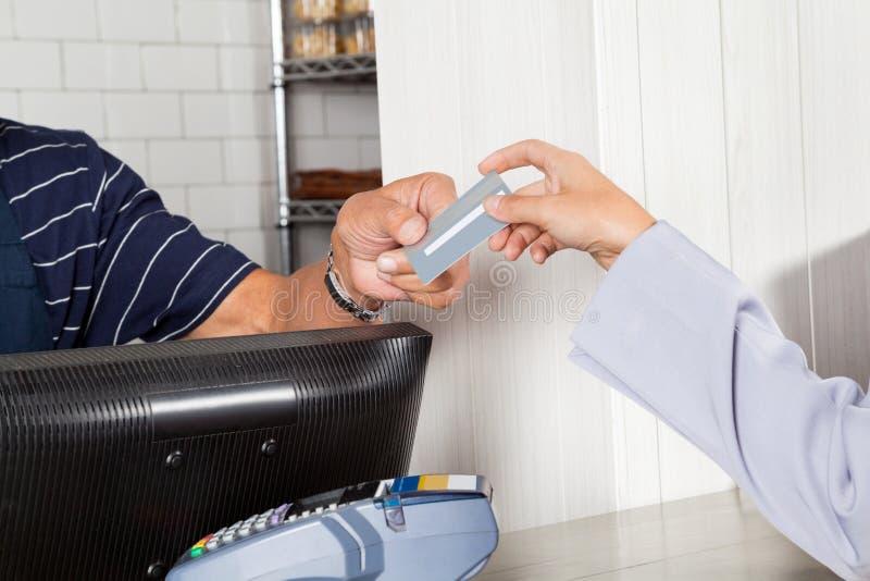 Client féminin effectuant le paiement par carte de crédit photo stock