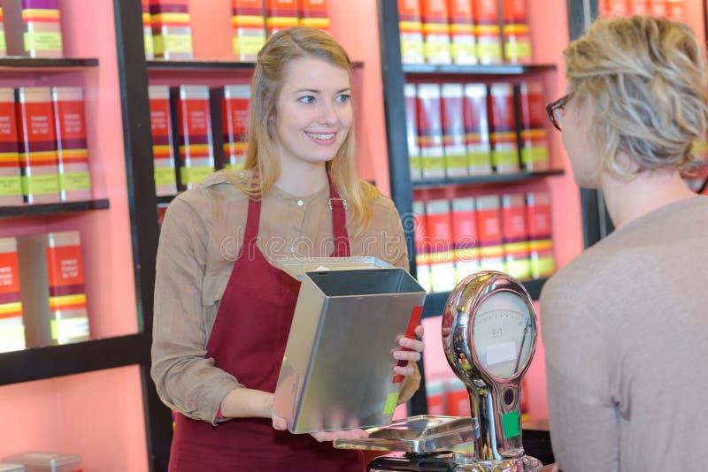 Client féminin gai sélectionnant des sortes de thé dans le magasin photo stock