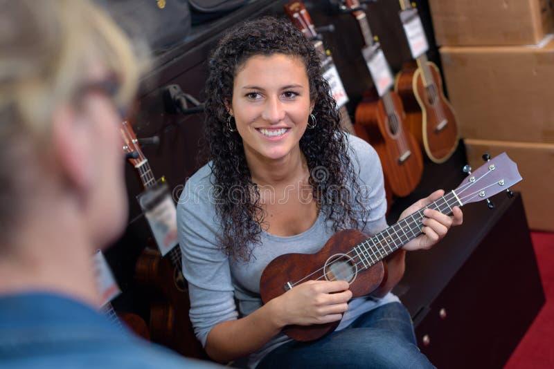 Client féminin heureux essayant de jouer la guitare dans le magasin images libres de droits