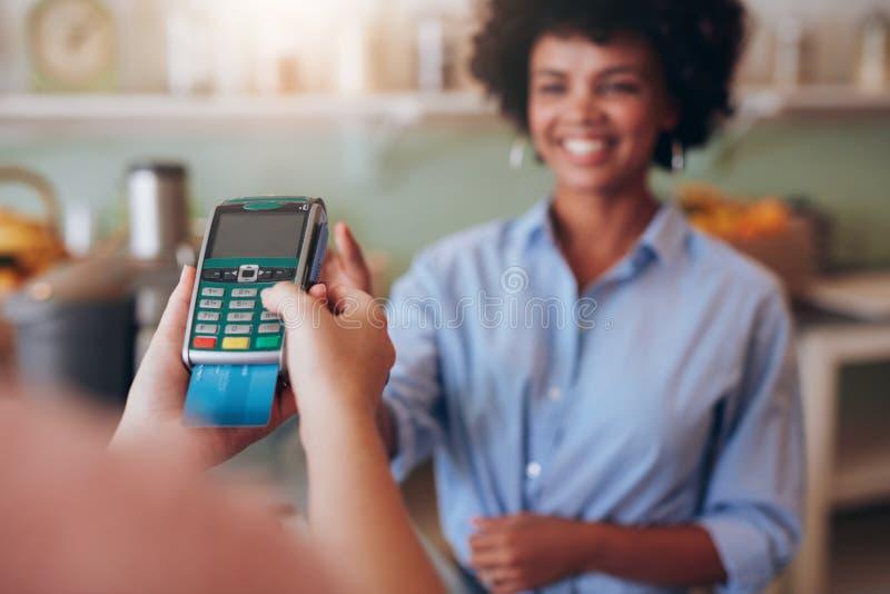 Client féminin payant par la carte de crédit au bar à jus photo stock