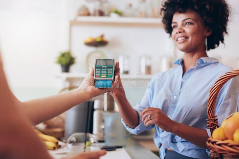 Client féminin payant son jus par la carte de crédit image libre de droits