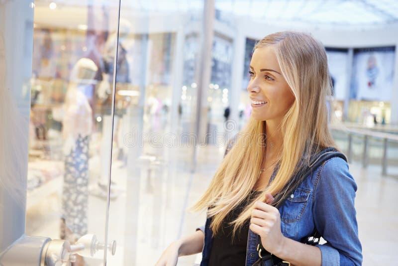 Client féminin regardant dans la fenêtre de magasin à l'intérieur du centre commercial photos stock