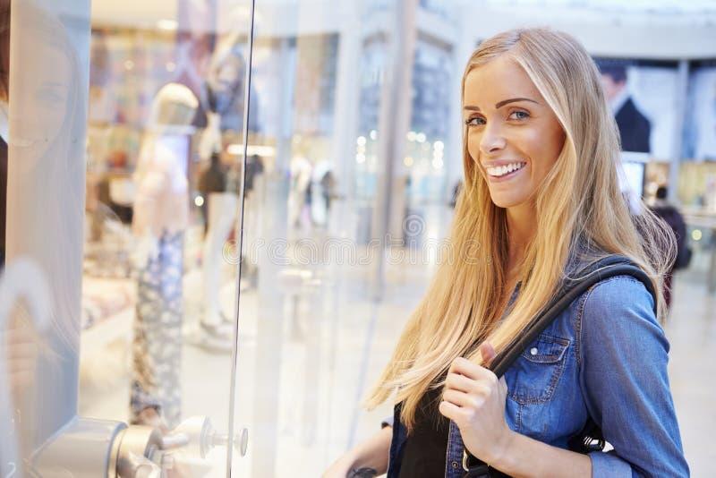 Client féminin regardant dans la fenêtre de magasin à l'intérieur du centre commercial photographie stock libre de droits