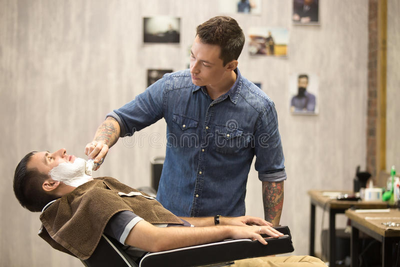 Client getting beard shaving in barber shop stock photography
