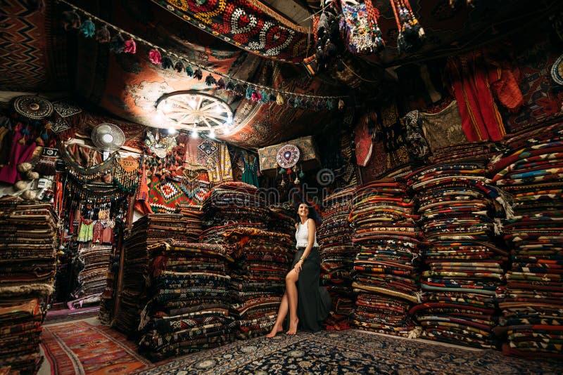 Client heureux de femme choisissant le tapis coloré dans le magasin de tapis image stock