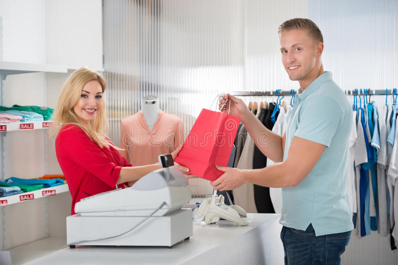 Client heureux prenant le panier de la vendeuse In Store photographie stock libre de droits