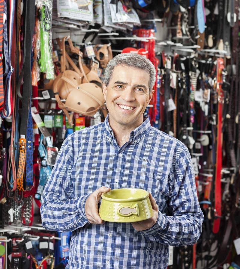 Client heureux tenant le bol de nourriture au magasin d'animal familier photographie stock libre de droits