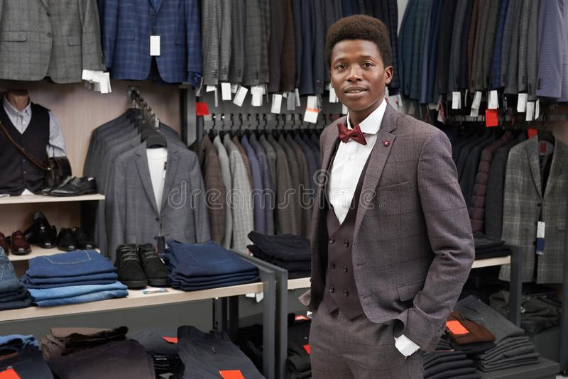 Client holding hand in pocket of pants posing in shop. Client of boutique holding hand in pocket of pants, looking at camera. Handsome man fitting and posing in royalty free stock photos