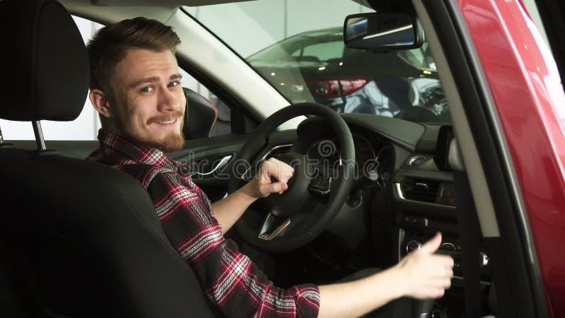 Client masculin beau joyeux montrant des pouces se reposant dans une nouvelle voiture au concessionnaire images libres de droits