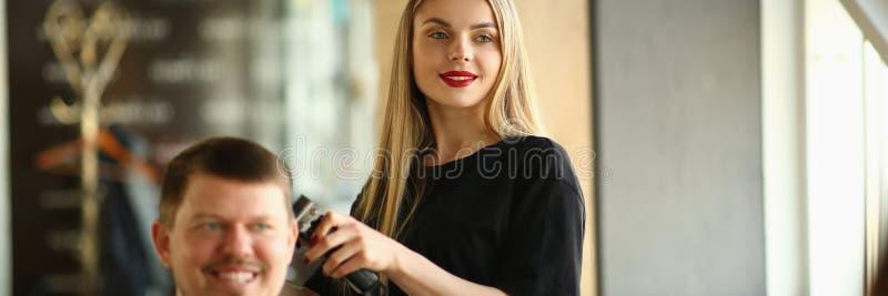 Client masculin de sourire de rasage de styliste en coiffure de jeune fille photos stock