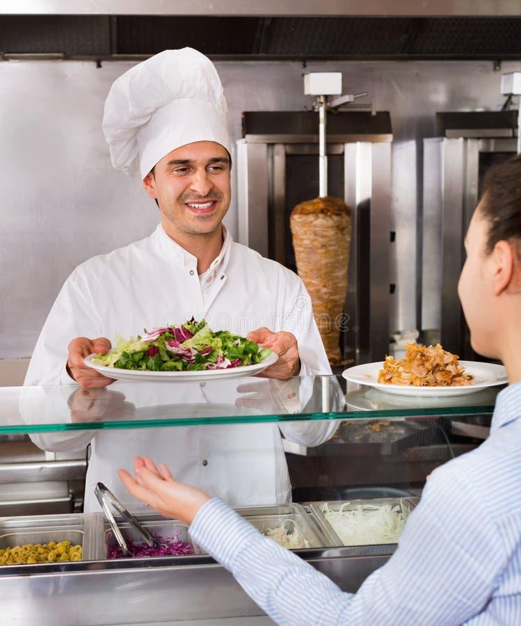 Client masculin heureux de portion de travailleur avec le sourire au shawarma photos stock