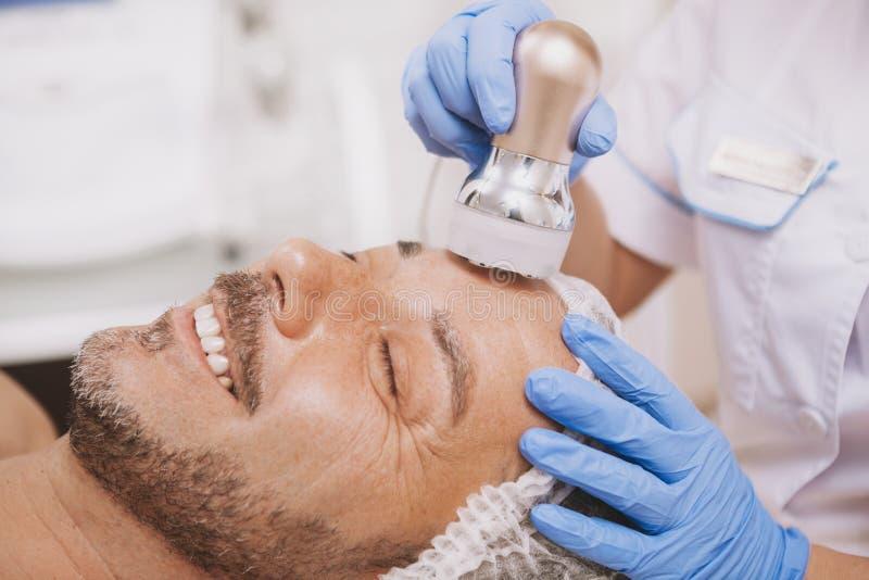 client masculin Mi-âgé bénéficiant du traitement de cosmétologie de matériel image stock