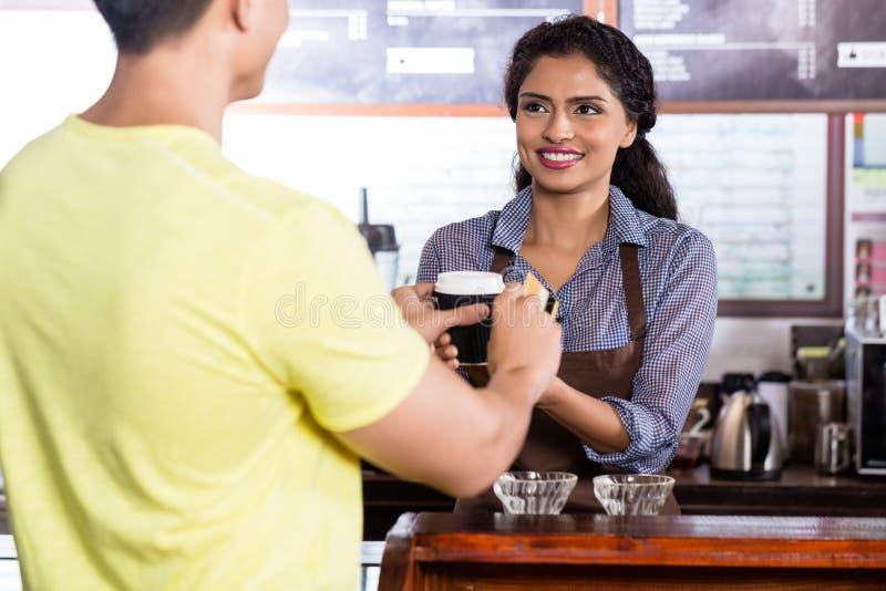 Client masculin payant le café avec la carte de crédit photos stock