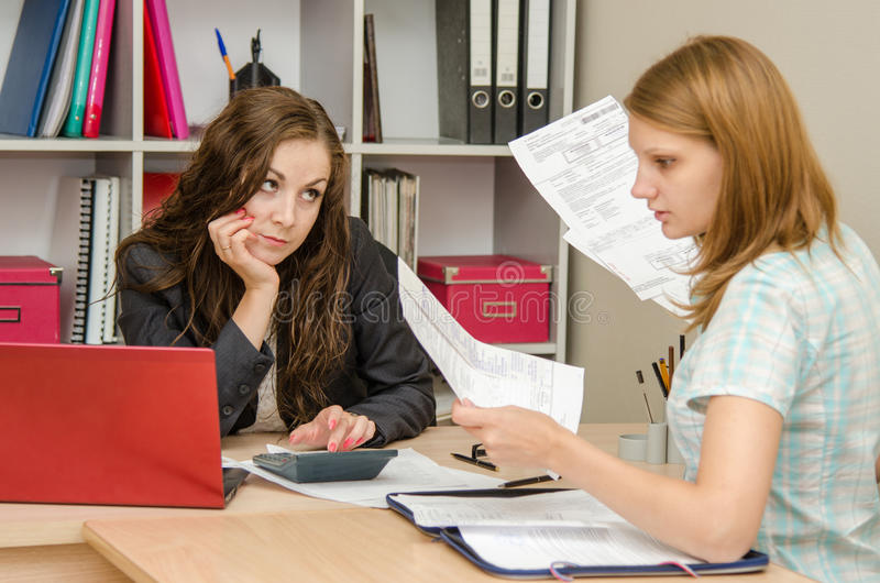 The client and the office specialist versed in the accounts. Young beautiful girl on reception at the office specialist stock image