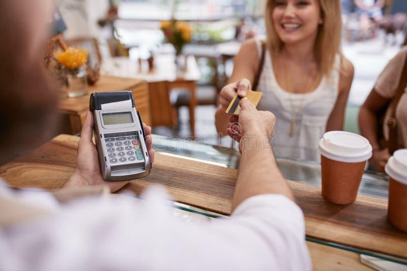 Client payant à un café avec la carte de crédit photos stock