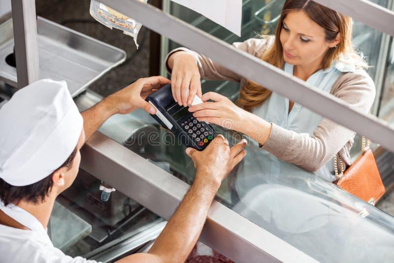 Client payant par Smartphone au boucher image stock