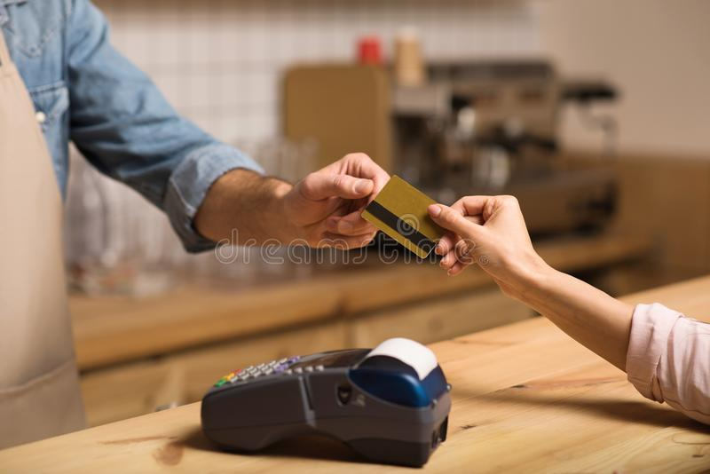 Client paying by credit card in cafe. Cropped shot of client paying by credit card with payment terminal in cafe royalty free stock photos