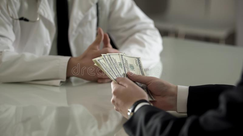 Client paying dollars cash to doctor for expensive operation, medical reform. Stock photo royalty free stock photography
