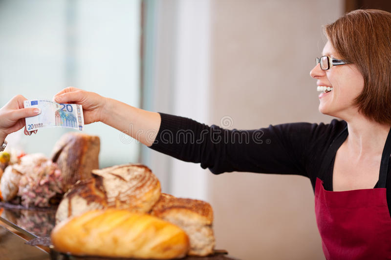 Client paying 20 euro in bakery. Smiling saleswoman receiving 20 euro in bakery stock photos